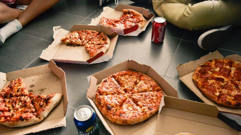 Kartons mit Pizza liegen auf dem Boden.