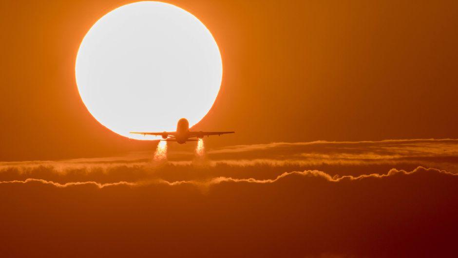 Flugzeug bei Sonnenuntergang mit leuchtendem Abgasstrahl.