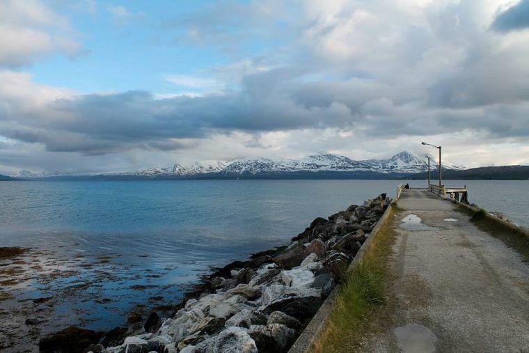 Blick auf einen Steg in Tromsø mit schneebedeckten Bergen im Hintergrund.
