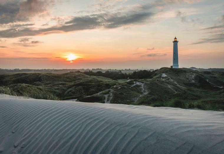 Sanddünen am Strand von Hvide Sande im Sonnenuntergang, im Hintergrund ein Leuchturm.