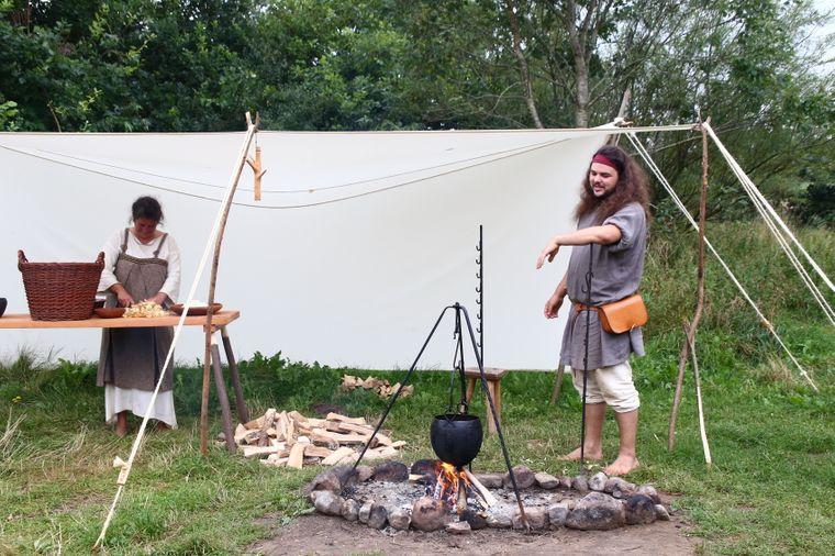 Bewohner des Ribe VikingeCenter beim Kochen überm Lagerfeuer.