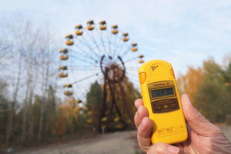 Jemand hält einen Geigerzähler in die Luft vor einem Riesenrad in der Geisterstadt Prypjat.