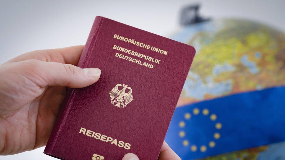 Ein deutscher Reisepass vor einem Globus.