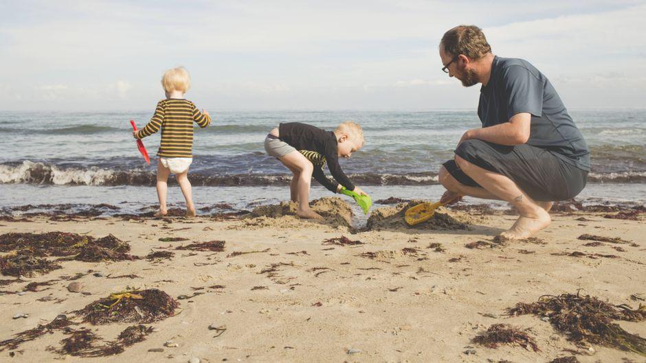 Eine Familie spielt am Ostsee-Strand. Die Ferientermine sind lange im Voraus festgelegt, könnten sie wegen Corona verschoben werden?