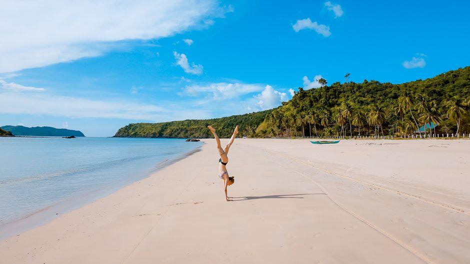Frau macht Handstand am Strand von Palawan, Philippinen.