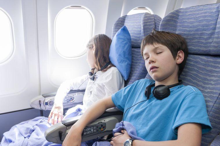 Zwei Kinder schlafen mit Kopfkissen, Decke und Kopfhörer in einem Flugzeug.