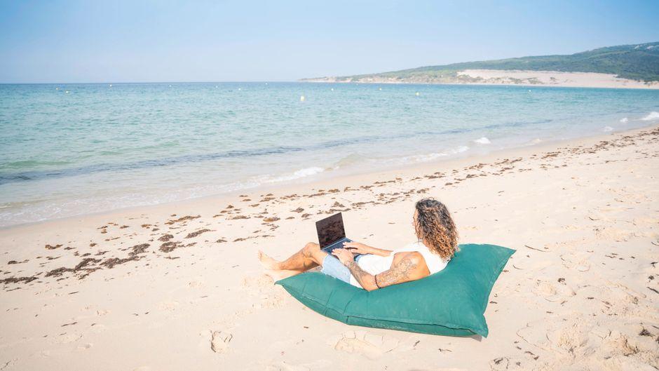 Mann mit seinem Laptop an einem Strand in Spanien.