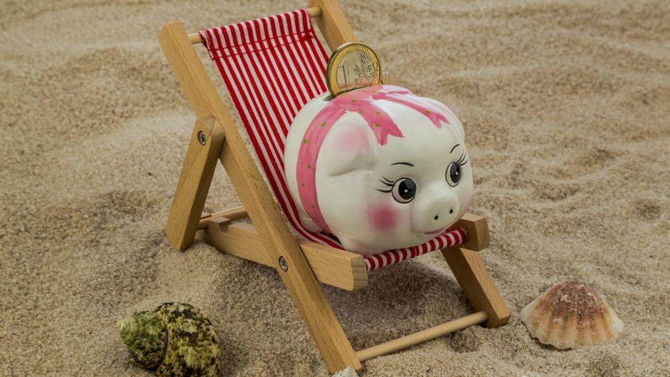 Das Sparschwein freut sich über jeden Euro, der nach dem Urlaub noch übrig ist.