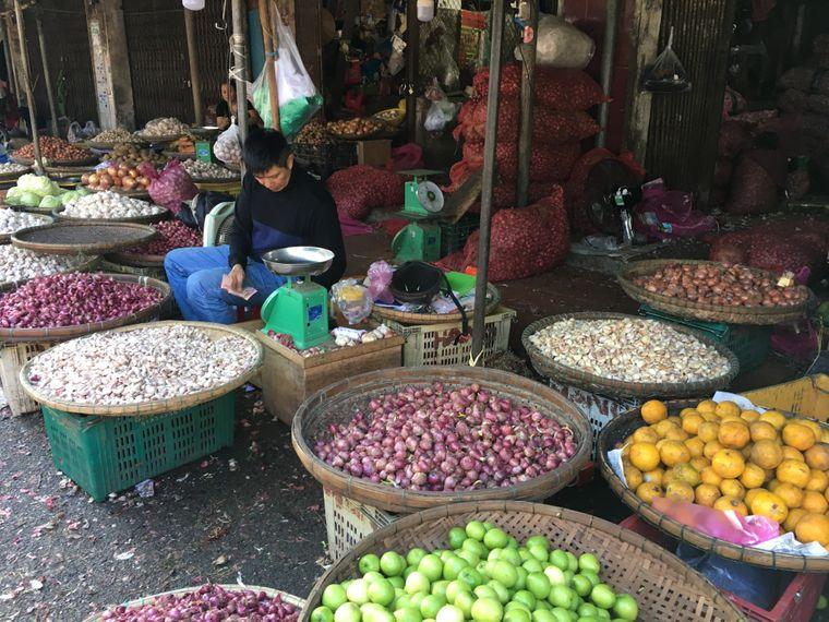 Mann verkauft Zwiebeln und Knoblauch auf dem Markt in Hue, Vietnam.
