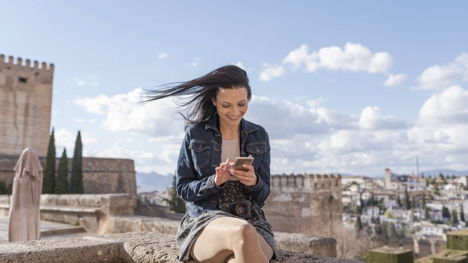 Junge Frau mit Handy in Granada in Spanien.