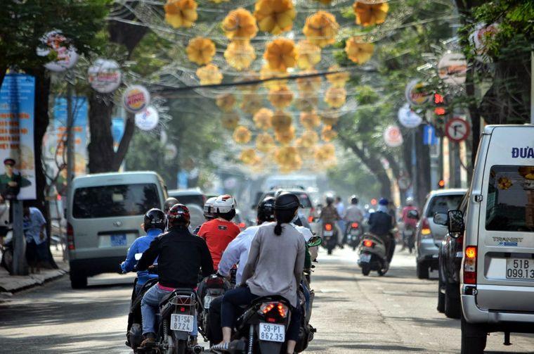 Roller und Autos auf der Straße in Vietnam unter geschmückten Bäumen.