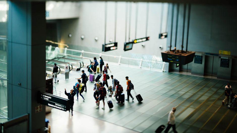 Menschen an einem Flughafen. Wohin wollen die Menschen im Jahr 2021 reisen – und wie? Die Reisetrends geben einen Ausblick.