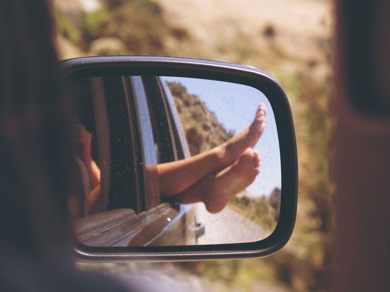 Füße ragen aus dem Autofenster, fotografiert im Rückspiegel