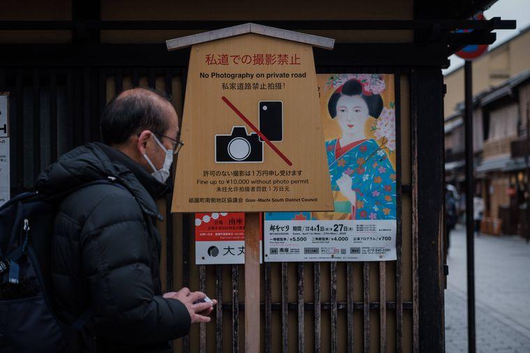 Ein Mann mit Mundschutz vor einem Schild, das das Fotografieren von Geishas verbietet, in Kyoto, Japan.