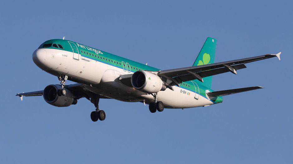 Ein Flugzeug von Aer Lingus vor blauem Himmel über London.