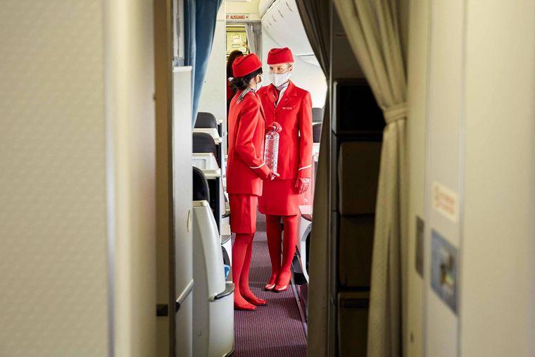 Zwei Stewardessen im Inneren eines Flugzeugs. Menschen mit Flugangst beobachten das Verhalten des Flugpersonals meist genau.
