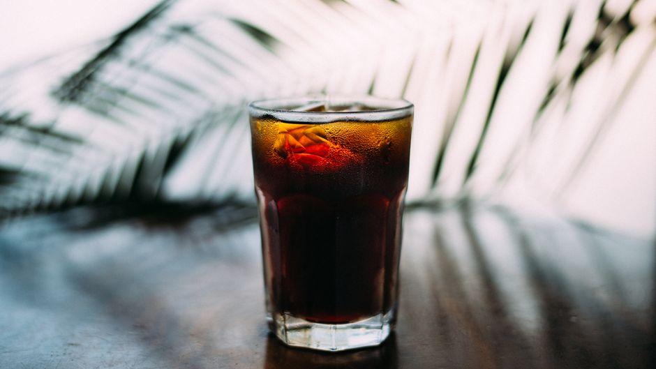 Ein Glas Cola steht auf einem Tisch vor einem Palmenblatt.