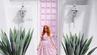 Frau posiert vor der pink Haustür in Palm Springs, die mit #thatpinkdoor einen Instagram-Hashtag hat.
