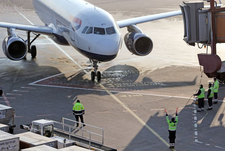 Der Ramp Agent weist ein Flugzeug der British Airways auf dem Vorfeld des Flughafens Berlin-Tegel in die Parkposition ein.