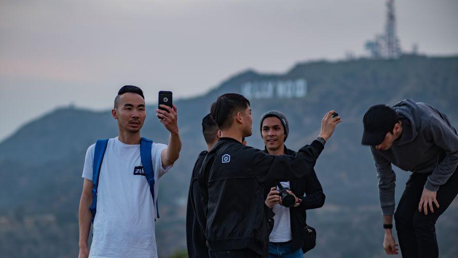 Eine Gruppe von Touristen fotografiert sich vor dem Hollywood-Sign.
