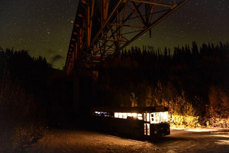 Ein Schulbuss steht unter einer Brücker und dem Sternenhimmel in Kanada.