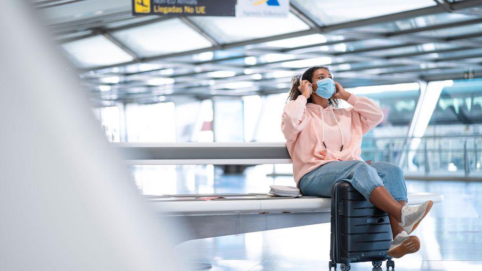 Eine Frau mit Mund-Nasen-Schutz sitzt auf ihrem Koffer am Flughafen. Immer mehr Reisen werden trotz Corona möglich. (Symbolbild)