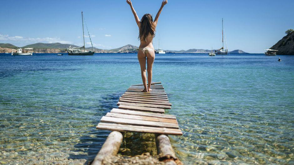 Frau im Bikini auf einem Steg auf Ibiza, Spanien