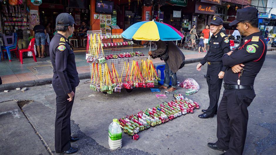 Polizisten in Bangkok fordern Straßenverkäufer auf, ihre Stände auf der Khao San Road zu räumen.