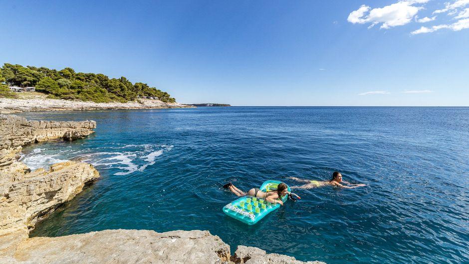 Eine Frau mit Kind und Luftmatratze in der Adria – wie sicher ist das Reisen aktuell? (Symbolfoto)