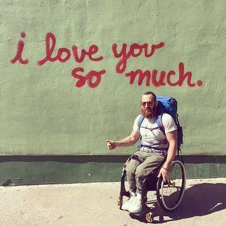 """Eamon in seinem Rollstuhl vor einer Wand mit der Aufschrift """"I love you so much""""."""