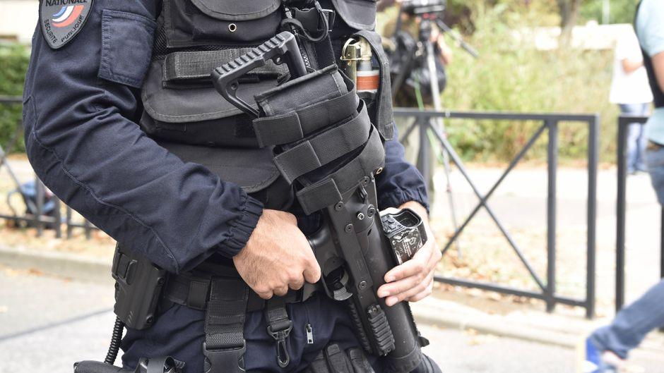 Ein bewaffneter Polizist steht in einem Pariser Vorort.