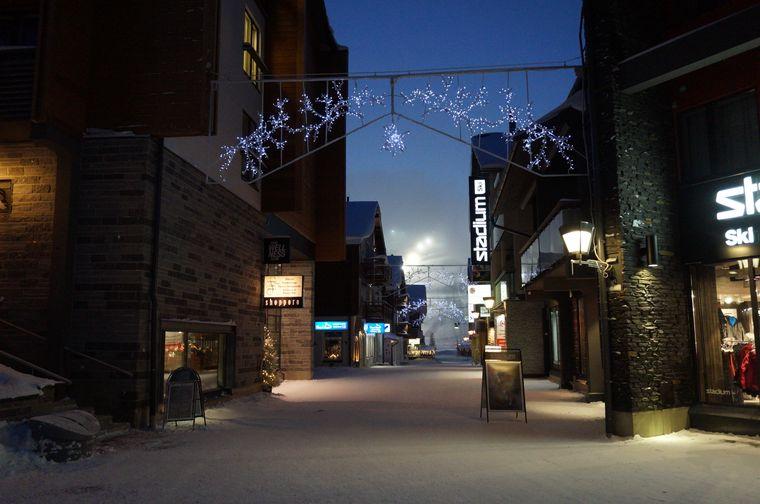 Einkaufststraße im Levi-Resort. Im Hintergrund leuchtet die Skipiste.