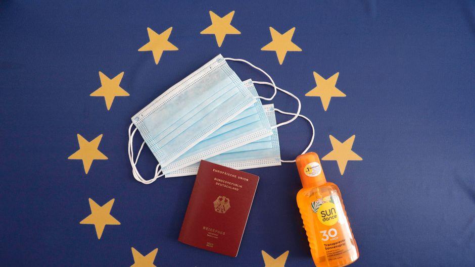 Auf einer Europafahne liegt ein Reisepass und Sonnenspray.