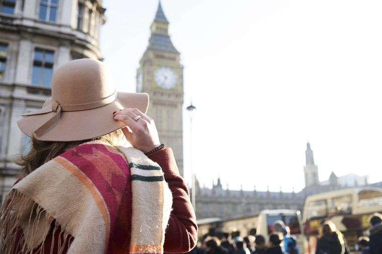 Eine Frau mit Hut steht vor dem Big Ben in London.