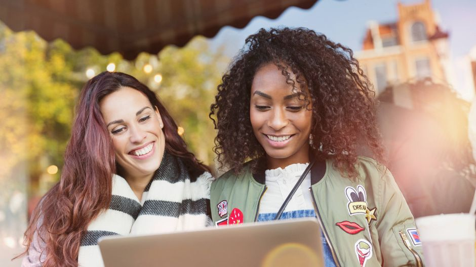 Zwei Frauen sitzen vor dem Laptop zur Reiseplanung