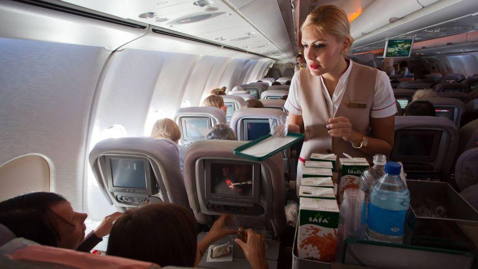 Eine Flugbegleiterin serviert im Flugzeug Getränke