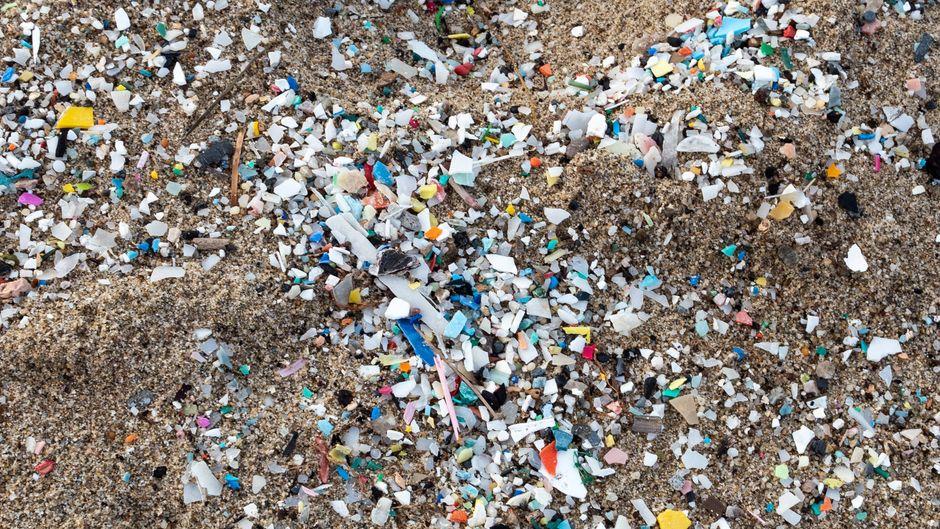 Kleine, bunte Plastikpartikel liegen auf einem Sandstrand.