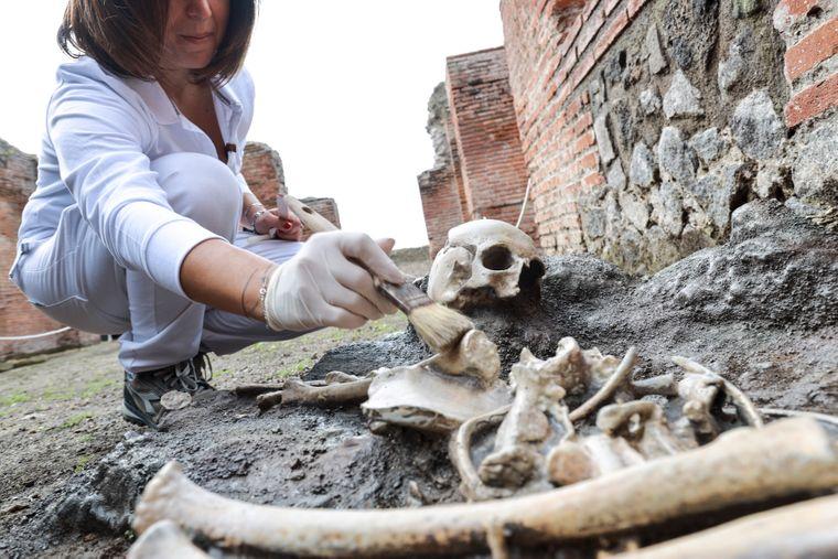 Eine Archäologin bei der Ausgrabungsstelle eines Skeletts.