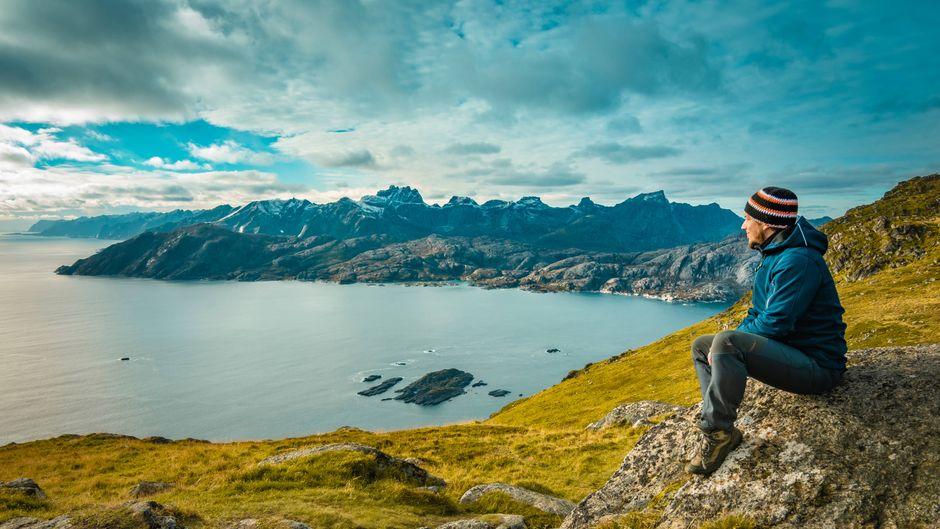 Eine Frau sitzt auf einem Felsen in Norwegen.