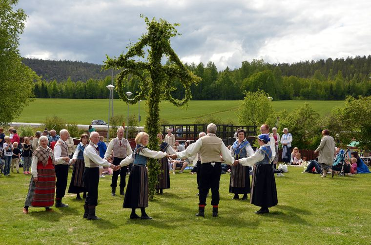 Traditionell gekleidete Schweden tanzen an Midsommar um den Maibaum.