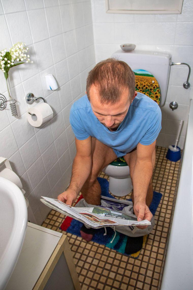 Mann liest Zeitung im Sitzen auf dem Klo.