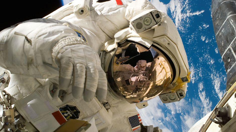 Das Bild zeigt einen amerikanischen Astronauten in seinem Raumfahrtanzug. Im Hintergrund und auf dem Visier seines Helmes wird zum Teil das Raumschiff gezeigt. Außerdem erscheint hinter ihm die Erde.