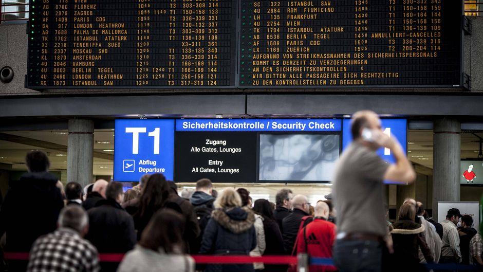 Menschen stehen vor einer Anzeigetafel am Flughafen.