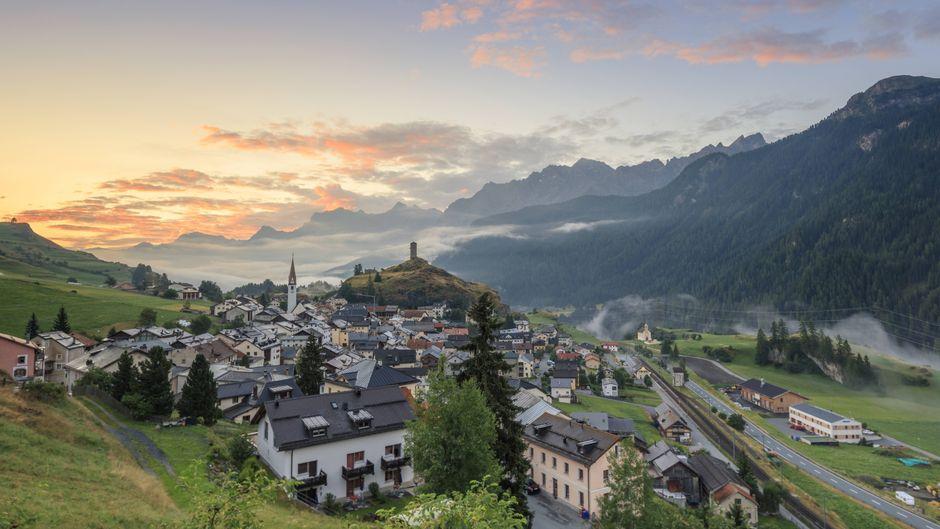 Rosafarbene Wolken hängen in der Dämmerung über dem Alpen-Dorf Ardez im Kanton Graubünden.