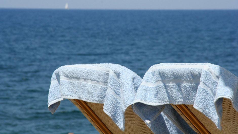Liegestühle mit Badehandtücher auf zwei Liegen mit Blick auf das Meer.