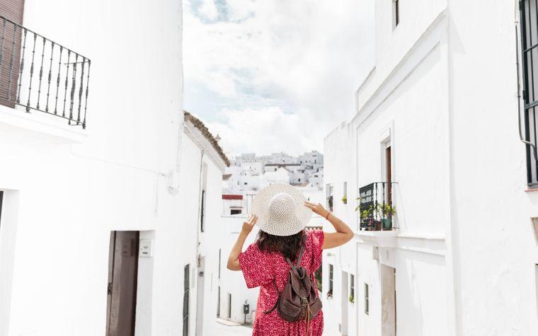 Eine Frau steht in einer Straße in einem Dorf mit weißen Häusern auf Rhodos.
