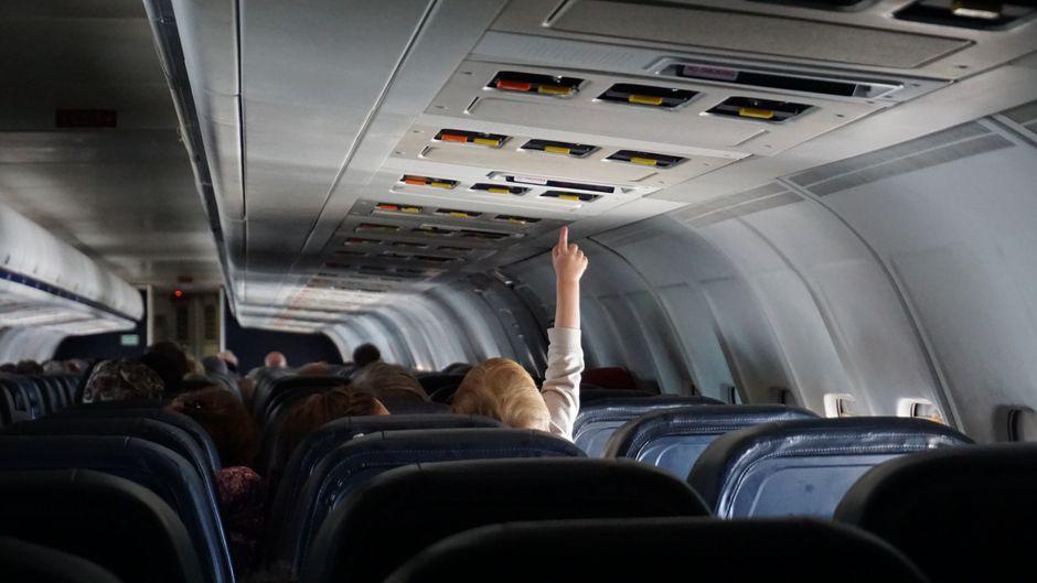 Ein Kind drückt einen Knopf über dem Sitzplatz im Flugzeug.