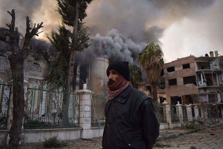 """Der erste Platz der Kategorie """"People of the World"""" geht an Mouneb Taim. Er zeigt eindrückliche Bilder aus Syrien – hier läuft ein Mann durch das zerstörte Douma."""