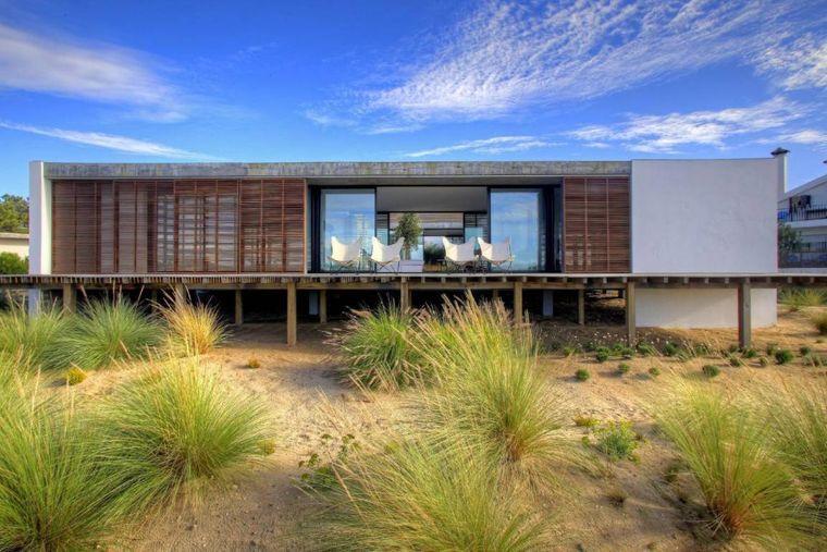 Diese Designvilla befindet sich in einer Dünenlage am Meer.
