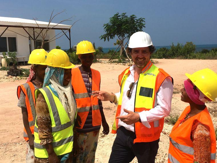 Fertighäuser nach deutschem Vorbild: Projektkeiter Sebastian Dietzold mit Arbeiterinnen auf der Baustelle in Sansibar